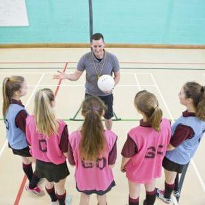 Gym teacher teaching high school students netball in gym class